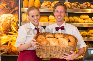 Zwei Bäcker in Bäckerei mit Brotkorb voller Brötchen