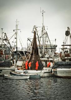 Fisherman crew fixing nets on fishing boat