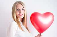Woman holding a red heart balloon