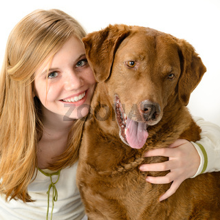 Young smiling girl with her playful dog