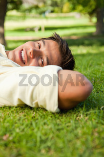 Man smiling while lying with the side of his head resting on his hands