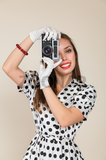Young woman making photos with vintage film camera