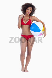 Smiling woman holding a beach ball and sunglasses