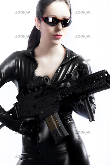 Brunette young sexy woman in latex with gun