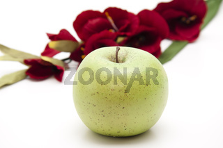 Grüner Apfel vor roter Blume