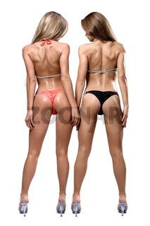 Two athletic girl wearing bikini posing over white background
