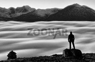 Wanderer blickt ueber das nebelverhuellte Atndalen zum Gipfel Rondslottet im Rondane Nationalpark, Hedmark