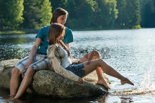 Couple sitting on rock sharing romantic moment
