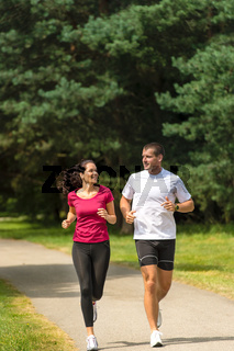 Young smiling couple running in park