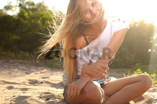 girl sitting near river against sun