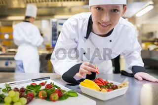 Happy chef preparing fruit salad