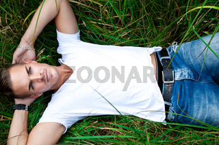 beautiful young man lying on green gras