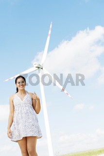 Teen girl next to wind turbine.