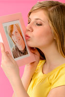 Young girl holding and kissing boyfriend's picture