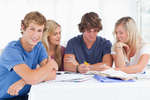 A group of students sitting together as they all study as one sits ahead a bit