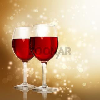 Glasses of Red Wine on Sparkling Golden Background