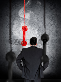 Businessman looking at hanging telephone receiver