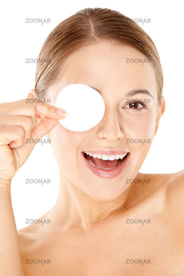 Laughing woman holding a cotton pad to her eye