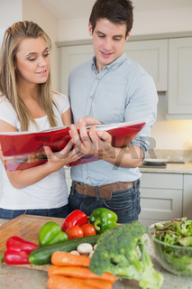 Couple reading cookbook together