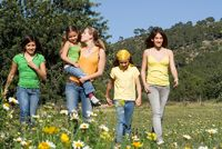 group of healthy girls or sisters walking in countryside