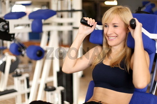 Attractive blonde woman weightlifting in a gym