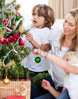Smiling Mother and her children decorating a Christmas tree