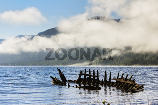 Wreck of old wooden ship on the Lake Teletsky in mountains.