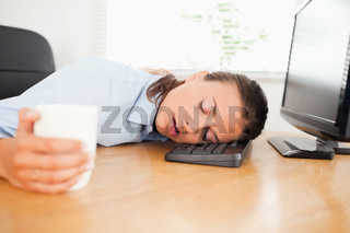 Sleeiping woman in an office holding coffee