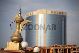 Typisch arabische goldene Teekanne vor Hochhaus mit Rolex-Logo am Dubai Creek in Dubai