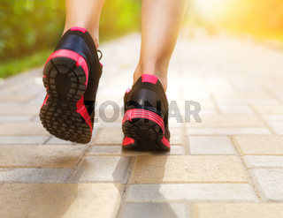 Runner feet running on road closeup on shoes