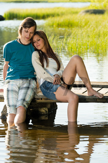 Teen couple sitting on water pier