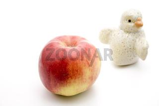 Roter Apfel und Keramik Vogel