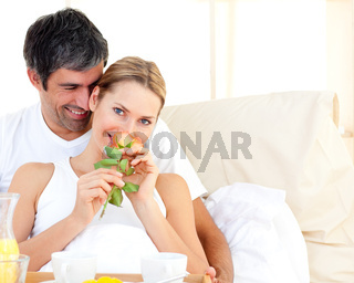 Close-up of couple having breakfast lying in the bed