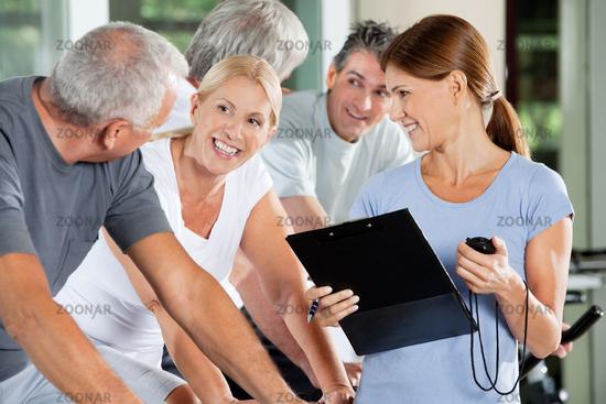 Lachende Senioren mit Fitnesstrainer