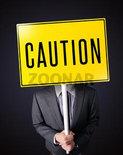 Businessman holding a caution sign