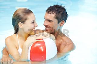 Paar im Pool mit Wasserball