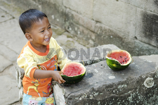 asian child eating fruit in cambodia