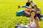 Students studying sitting on grass in park