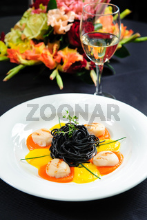 Black pasta with meat, garnished with sauce and  herbs close-up