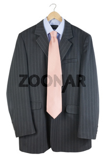 The old striped  jacket and pink tie hang on a hanger