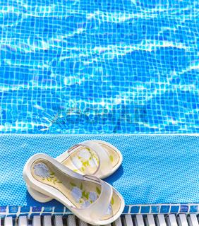 beach slippers on a pool edge