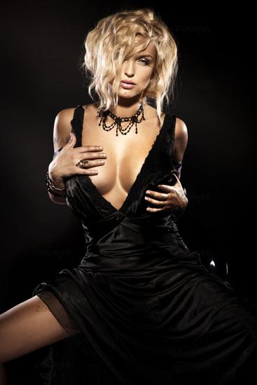 Sexy blonde beauty sitting in elegant black dress