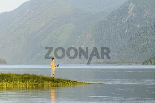 Beautiful reservoir in Siberia and the fisherman ashore