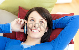 Beautiful teen girl talking on phone lying on a sofa