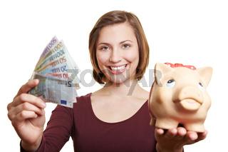 Lachende Frau mit Geldscheinen und Sparschwein
