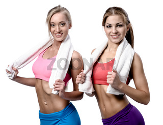 Two beautiful girls after workout with towels isolated on white background
