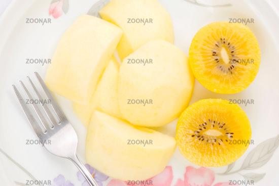 Golden kiwi fruit and sliced apple with fork