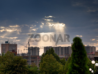 sun rays through clouds illuminate new buildings