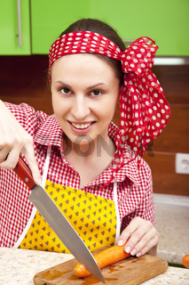 Woman in the kitchen with knife and vegetables