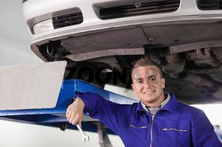 Mechanic holding a spanner below a car